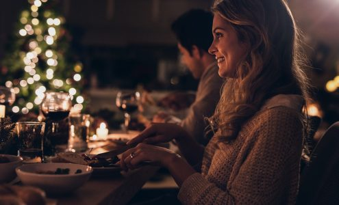 Beautiful young woman sitting with family and having christmas dinner. Family celebrating christmas together at home.